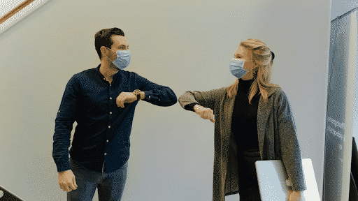 Image of two people in masks touching elbows